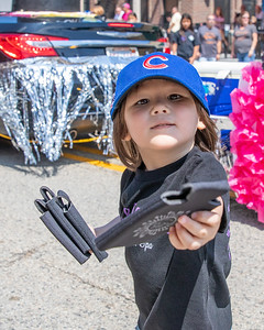 Riley Nguyen (age 3) from Johnsburg passes out can koozies to the crowd on Green Street during the 2019 Fiesta Days Parade Sunday, July 21, 2019 in McHenry. KKoontz – For Shaw Media