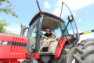 Candace H. Johnson-For Shaw Media Wyatt Rabey, 22, of Round Lake shows his nephew, Anthony, 3, of Round Lake Beach the inside of a Case MX 285 tractor during Touch-a-Truck at the Metra parking lot next to the Round Lake Beach Cultural & Civic Center. (7/20/19)