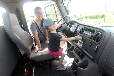 Candace H. Johnson-For Shaw Media Abi Pogvara, of Round Lake Beach watches her daughter, Anora, 3, pull on a knob inside of a Lake Villa Township Highway Dept. dump truck during Touch-a-Truck at the Metra parking lot next to the Round Lake Beach Cultural & Civic Center. (7/20/19)