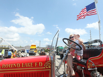 Candace H. Johnson-For Shaw Media Rachael Sotirovic, of Hainesville sits in a 1929 firetruck with her son, Gavin, 1, during Touch-a-Truck at the Metra parking lot next to the Round Lake Beach Cultural & Civic Center. (7/20/19)