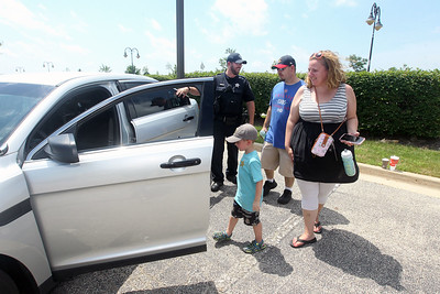 Candace H. Johnson-For Shaw Media Robert Gannon, patrolman with the Round Lake Beach Police Dept., talks with Tom and Nicole Ozog, of Mundelein and their son, Jonathan, 4, about the police department's unmarked squad car during Touch-a-Truck at the Metra parking lot next to the Round Lake Beach Cultural & Civic Center. (7/20/19)