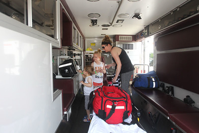 Candace H. Johnson-For Shaw Media Maggie Kukawski, of Antioch and her children Brady, 3, and Madi, 6, look inside an ambulance during Touch-a-Truck at the Metra parking lot next to the Round Lake Beach Cultural & Civic Center. (7/20/19)