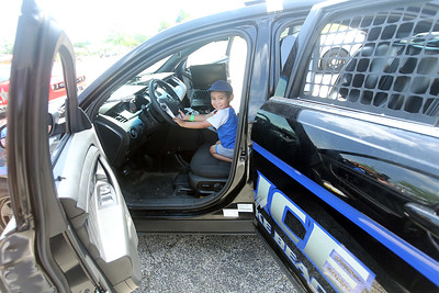 Candace H. Johnson-For Shaw Media Isaac Vitor, 3, of Kenosha, Wis., sits in a Round Lake Beach Police Dept. squad car during Touch-a-Truck at the Metra parking lot next to the Round Lake Beach Cultural & Civic Center. (7/20/19)