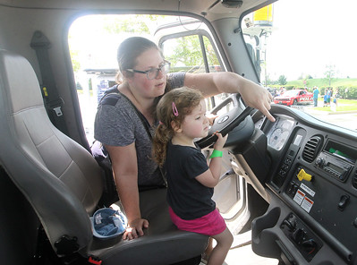 Candace H. Johnson-For Shaw Media Abi Pogvara, of Round Lake Beach shows her daughter, Anora, 3, the inside of a Lake Villa Township Highway Department dump truck during Touch-a-Truck at the Metra parking lot next to the Round Lake Beach Cultural & Civic Center. (7/20/19)