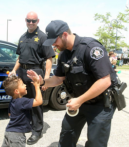 Candace H. Johnson-For Shaw Media Augustine Gomez, 4, of Grayslake gets a high-five from Robert Gannon, patrolman, with Commander Paul Grace, beside them, both with the Round Lake Beach Police Dept. during Touch-a-Truck at the Metra parking lot next to the Round Lake Beach Cultural & Civic Center. (7/20/19)