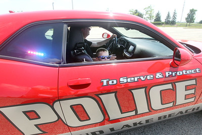 Candace H. Johnson-For Shaw Media Gary Lunn, commander of the investigation division for the Round Lake Beach Police Dept., gives a ride to Milan Czerwinski, 3, of Volo in a Dodge Challenger during Touch-a-Truck at the Metra parking lot next to the Round Lake Beach Cultural & Civic Center. (7/20/19)