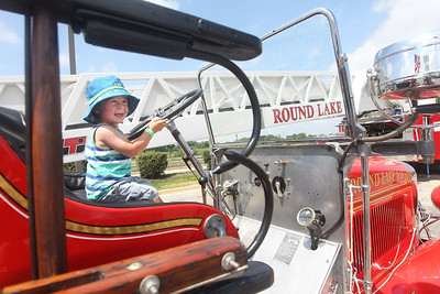 Candace H. Johnson-For Shaw Media Wes Racine, 2, of Libertyville sits in a 1929 fire truck during Touch-a-Truck at the Metra parking lot next to the Round Lake Beach Cultural & Civic Center. Wes was at the event with his mother, Kim, and sister, Paige, 4.(7/20/19)