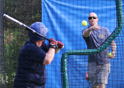 Candace H. Johnson-For Shaw Media Tim Nockels, of Vernon Hills, (on right) assistant coach, delivers a pitch to Dominick Deslauriers, 39, of Libertyville in the batting cage during the Special Recreation Association of Central Lake County (SRACLC) softball practice for the Crusaders Silver team at Deerpath Park in Vernon Hills. The Crusaders Silver team was practicing for their district tournament in Elgin on August 3rd. (7/23/19)