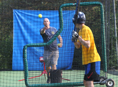 Candace H. Johnson-For Shaw Media Tim Nockels, of Vernon Hills, assistant coach, delivers a pitch as he works with Andrew Koppel, 19, of Lake Zurich, in the batting cage during the Special Recreation Association of Central Lake County (SRACLC) softball practice for the Crusaders Silver team at Deerpath Park in Vernon Hills. The Crusaders Silver team was practicing for their district tournament in Elgin on August 3rd. (7/23/19)