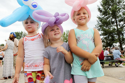 Candace H. Johnson-For Shaw Media Peyton Starke, 4, of Antioch and her sisters, Teagan, 3, and Natalie, 6, show off their balloon hats during Antioch's Taste of Summer in downtown Antioch. (7/21/19)