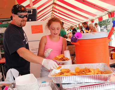 Candace H. Johnson-For Shaw Media Lance Mitchell, of Antioch gets some help from Mackenzy Lass, 10, of Lakemoor, both with The Lodge of Antioch-Northwoods Pub & Eatery, putting homemade potato chips into a take out container for their sloppy chips meal during Antioch's Taste of Summer in downtown Antioch. (7/21/19)