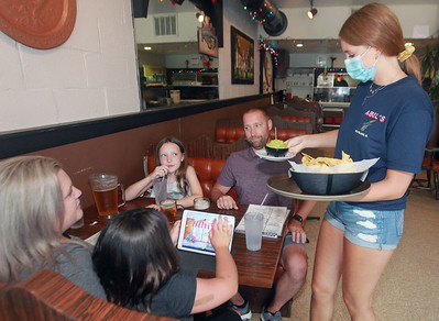 Candace H. Johnson-For Shaw Media Jenna Rickman, 16, of Arlington Heights serves guacamole and chips to Melissa and Mike Brodeur as they sit with their children, Caitlyn, 10, and Lauren, 7, all of Grayslake, at Abel's Restaurant in downtown Grayslake.  (7/6/20)