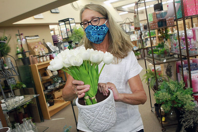 Candace H. Johnson-For Shaw Media Shelly Hastings, of Grayslake, floral designer/sales, puts some silk tulips in a vase at Hannah's on Lake Street in downtown Antioch. (6/26/20)