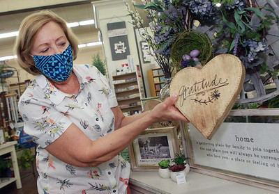Candace H. Johnson-For Shaw Media Jane Marski, of McHenry, owner, shows a gratitude sign featured at Hannah's on Lake Street in downtown Antioch. (6/26/20)