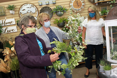 Candace H. Johnson-For Shaw Media Debbie Harding and Kim Dunlap, both of McHenry look at silk wreaths as they are helped by Shelly Hastings, of Grayslake, floral designer/sales, at Hannah's on Lake Street in downtown Antioch. (6/26/20)
