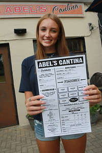 Candace H. Johnson-For Shaw Media Jenna Rickman, 16, of Arlington Heights shows the menu of dishes served at Abel's Restaurant in downtown Grayslake. Jenna works at the restaurant with her family and her grandfather, Abel, is the owner.(7/7/20)