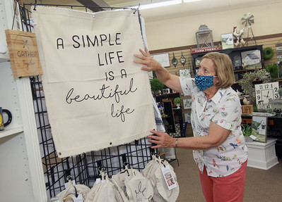 Candace H. Johnson-For Shaw Media Jane Marski, of McHenry, owner, straightens out a display featuring dish covers and towels at Hannah's on Lake Street in downtown Antioch. (6/26/20)