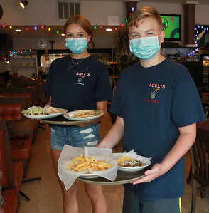Candace H. Johnson-For Shaw Media Jenna Rickman, 16, of Arlington Heights and her brother, Kyle, 14, wear masks as they serve a family their meals at Abel's Restaurant in downtown Grayslake.  (7/6/20)