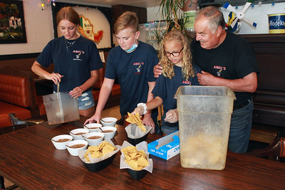 Candace H. Johnson-For Shaw Media Abel Bonilla, of Arlington Heights, owner, (on right) works with his grandchildren, Jenna Rickman, 16, of Arlington Heights and her siblings, Kyle, 14, and Taylor, 11, as they make chips and salsa at Abel's Restaurant in downtown Grayslake.  (7/6/20)