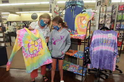 Candace H. Johnson-For Shaw Media Jane Marski, of McHenry, owner, shows her granddaughter, Kaia Sasak, 10, of Johnsburg a Puppie Love long sleeve shirt she features at Hannah's on Lake Street in downtown Antioch. (6/26/20)