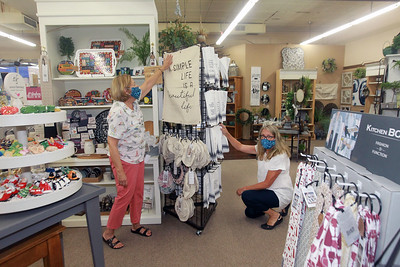 Candace H. Johnson-For Shaw Media Jane Marski, of McHenry, owner, and Shelly Hastings, of Grayslake, floral designer/sales, work on a display of dish covers and towels together at Hannah's on Lake Street in downtown Antioch. (6/26/20)
