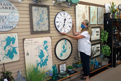 Candace H. Johnson-For Shaw Media Shelly Hastings, of Grayslake, floral designer/sales, adjusts a wall clock featured at Hannah's on Lake Street in downtown Antioch. (6/26/20)