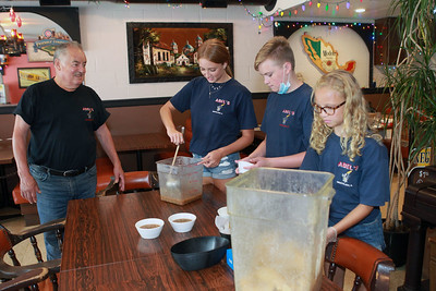 Candace H. Johnson-For Shaw Media Abel Bonilla, of Arlington Heights, owner, watches his grandchildren, Jenna Rickman, 16, Kyle, 14, and Taylor, 11, prepare chips and salsa at Abel's Restaurant in downtown Grayslake.  (7/6/20)