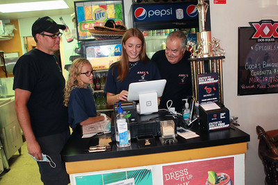 Candace H. Johnson-For Shaw Media Andy Rickman, of Arlington Heights, his daughters, Taylor, 11, and Jenna, 16, and their grandfather, Abel Bonilla, owner, work at the cash register at Abel's Restaurant in downtown Grayslake.  (7/7/20)