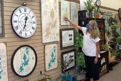 Candace H. Johnson-For Shaw Media Shelly Hastings, of Grayslake, floral designer/sales, talks about a wooden Chain O' Lakes Illinois custom map  featured at Hannah's on Lake Street in downtown Antioch. (6/26/20)