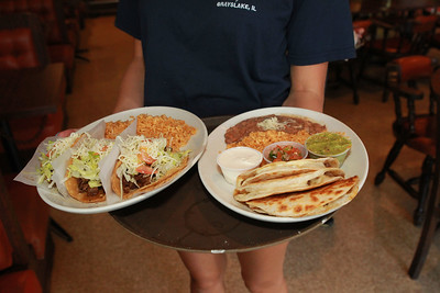 Candace H. Johnson-For Shaw Media Jenna Rickman, 16, of Arlington Heights serves a family their meals including a taco plate and quesadillas at Abel's Restaurant in downtown Grayslake.  (7/7/20)