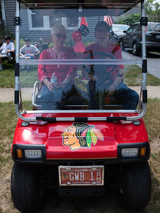 """McHenry residents for 69 years, Kathy and Gary Baseley wait along Main Street in a modified """"street legal"""" golf cart for the start of the Fiesta Days Parade on Sunday, July 18, 2021 in McHenry, IL.  A long-time Chicago Blackhawks fan, Gary decorated the golf cart in Blackhawks colors and emblems to support his favorite team.  Kathy and Gary have been married for 59 years."""