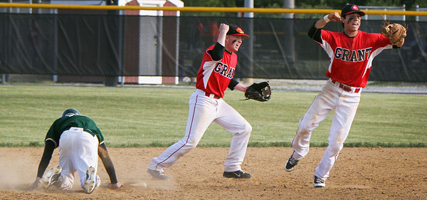 John Konstantaras/For Shaw Media Grant secondbaseman Jacob Adams (center) and shortstop Jordan Villareal (right) celebrate after tagging on Crystal Lake South's Max Meitzler (9) on a game ending 1-3-6 triple play in their IHSA Class 4A Sectional Semifinal game at Peterson Park in McHenry Friday June 1, 2012. The Bulldogs won the game 5-2.  John Konstantaras photo for the Northwest Herald