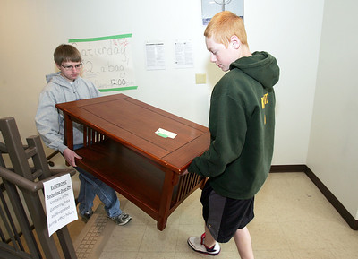 H. Rick Bamman - hbamman@shawmedia.com Bethany Lutheran church teenage members Erik Kountz (left) and Brian Kountz move a table they found at the church's garage sale Friday.