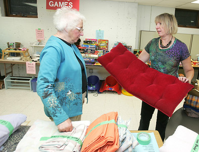 H. Rick Bamman - hbamman@shawmedia.com Long time parishioners of Bethany Lutheran Church Corrine Zoellick (left) and Debbie Berdis arrange cushions and pillows duringt the church's garage sale Friday. Pastor Carrie Smith said the way her church tries to  attract and keep people is by having the parishioners choose what they want to do in terms of service or activities. Zoellick has been a church member 47 years, Berdis 33 years.