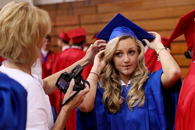 Mike Greene - mgreene@shawmedia.com Harmony Kendzora gets help fixing her cap prior to the start of commencement ceremonies for Marian Central Catholic High School Friday, June 1, 2012 in Woodstock.