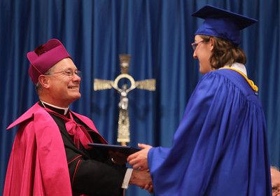 Mike Greene - mgreene@shawmedia.com Bishop David J. Malloy shakes hand with Elizabeth Reckamp while handing out diplomas during commencement ceremonies for Marian Central Catholic High School Friday, June 1, 2012 in Woodstock.