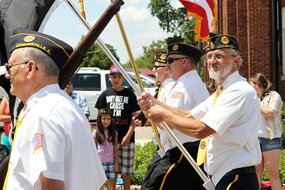 Mike Greene - mgreene@shawmedia.com Members of the American Veterans march carrying flags during the 71st Annual Milk Days Parade Saturday, June 2, 2012 in Harvard.