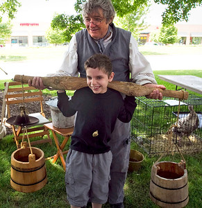"John Konstantaras/for the Northwest Herald Bob Paine of Crystal Lake helps Dominick Olandese, 10 of Woodstock, as he tries on a harness to carry water buckets at the ""A Day on the Farm"" event Sunday."