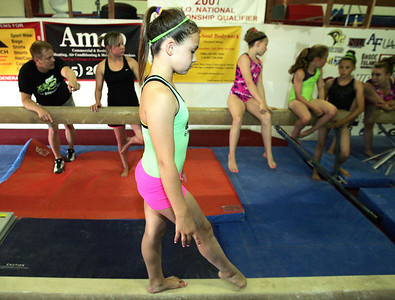 H. Rick Bamman - hbamman@shawmedia.com Trinity Gymnastics student Katarina Schmid practices on the beam as owner Chris Riegel (cq) (far left) and assistant coach Heather Morley direct other students at thefacility in Lake in the Hills.