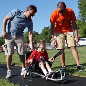 Mike Greene - mgreene@shawmedia.com Rich Martinez and Dave Dauphin help guide Ethan Martinez, 10 of Algonquin, while trying out a roller hockey system before the 5th Annual Run & Roll Track Meet Wednesday, June 6, 2012 at McCracken Field in McHenry. The event included participants of all ages with physical and visual disabilitie.
