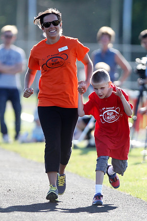 Mike Greene - mgreene@shawmedia.com Sarah Iuorio, of Palatine, helps guide Ethan Martinez, 10 of Algonquin, while racing during the 5th Annual Run & Roll Track Meet Wednesday, June 6, 2012 at McCracken Field in McHenry. The event included participants of all ages with physical and visual disabilitie.