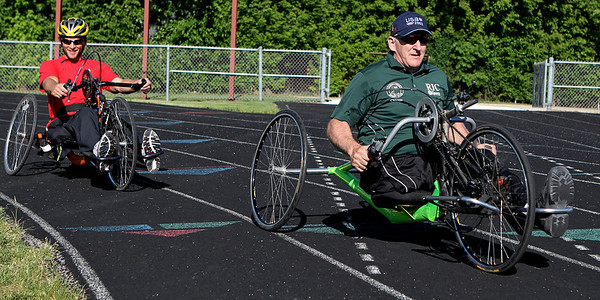 Mike Greene - mgreene@shawmedia.com Adam Finney (left) rides behind Patrick Byrne, a member of the gold-medal winning U.S. Sled Hockey team from the 2002 Paralympic Games, while showing off hand cycles before the 5th Annual Run & Roll Track Meet Wednesday, June 6, 2012 at McCracken Field in McHenry. The event included participants of all ages with physical and visual disabilitie.