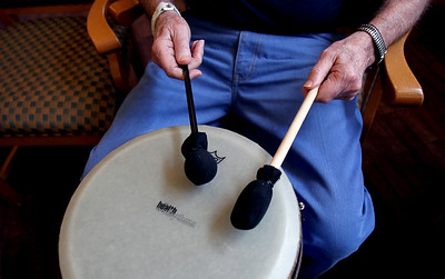Sarah Nader - snader@shawmedia.com A resident beats on the drum while participating in a therapeutic drum circle for residents at Fox Point Manor Assisted Living Facility in McHenry on Thursday, June 7, 2012.