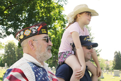 Morgan Ellingson - mellingson@shawmedia.com VFW 5th District Commander Ken Sambarski (cq), (left), and Chris O'Connor, (right), holding his daughter, Sheridan, watch as the newly restored Civil War statue is placed on it's monument in Union Cementery, Friday, June 8, 2012. O'Connor is a member of the Crystal Lake Historical Society Restoration Committee.