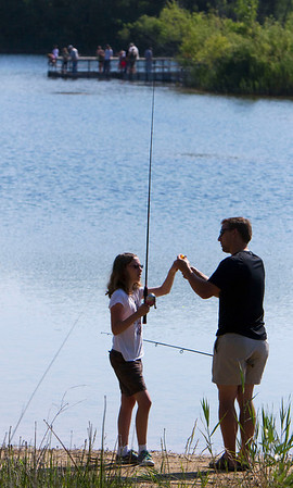 """Ryan Frank, from Algonquin, helps his daughter Julia, 11, during the McHenry County Conservation District's """"Hooked on Fishing"""" family event on Lake Atkins at The Hollows in Cary Sunday June 10, 2012.  John Konstantaras photo for the Northwest Herald"""