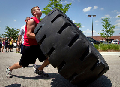 Tim Farbiak, 15 from Huntley, flips a 700 pound tire during the Strongman competition in the parking lot at Buffalo Wild Wings in Crystal Lake Sunday June 10, 2012.  John Konstantaras photo for the Northwest Herald