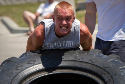 J.T. Mitchell, 17 from Cary, flips a giant tire during the Strongman competition in the parking lot at Buffalo Wild Wings in Crystal Lake Sunday June 10, 2012.  John Konstantaras photo for the Northwest Herald