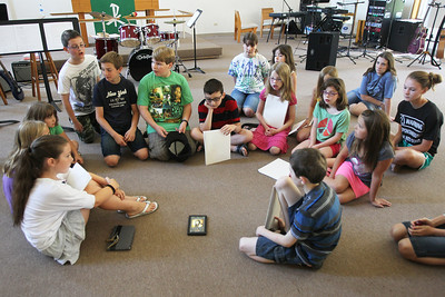 Mike Greene - mgreene@shawmedia.com Participants at Rock Jam Summer Camp huddle around to listen a popular version of the song they were performing Tuesday, June 12, 2012 at St. Barnabas Lutheran Church in Cary. The camp offers kids from 3rd-8th grade a chance to play music with others in a rock band environment and improve their music skills.