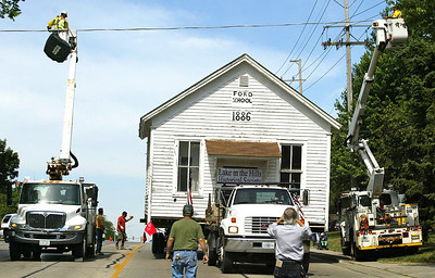 H. Rick Bamman - hbamman@shawmedia.com ComEd linemen keep watch as the Ford School house rolls under a power line on Algonquin Road Friday morning. The Lake in the Hills Historical Society moved the historic building from Algonquin back to Ford School Park, 302 Ramble Rd. in Lake in the Hills. Equipment to move the school was donated, along with excavation and tree services.