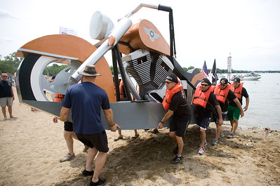"Mike Greene - mgreene@shawmedia.com The 8-man crew of the ""Made in USA"" carry their boat out of the water after a decisive first-round victory during the 28th Annual America's Cardboard Cup Regatta Saturday, June 23, 2012 at Main Beach in Crystal Lake. Members of the team estimated about 400 hours of work went into the creation of the boat."